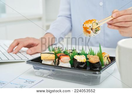 Close-up shot of busy white collar worker sitting in front of computer and eating sushi with help of chopsticks
