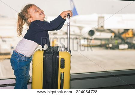 Happy baby carries your luggage at the airport terminal. Flying for holliday, traveling with you luggage safety through Singapore airport