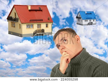 Pensive thinking young man in red sweater, choice between big and small house