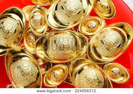 group of golden ingots on red tray at red background.Chinese new year concept,leave space for adding text.Chinese Language on ingot mean wealthy