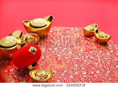 Chinese new year decoration,close up golden ingots ( ang pow )and lamp on red oriental pattern fabric hexagon box with chinese style pattern on red,Chinese Language mean Happiness and wealthy