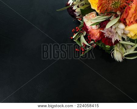 Orange and red autumn flowers and berries on dark background. Symbol of deep feelings and elation. Copyspace concept