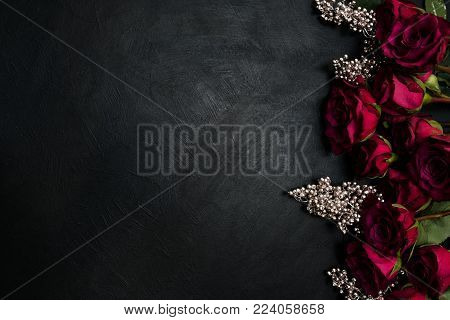 Burgundy or wine red roses and silver decor on dark background. True love passion and desire. Copy space concept