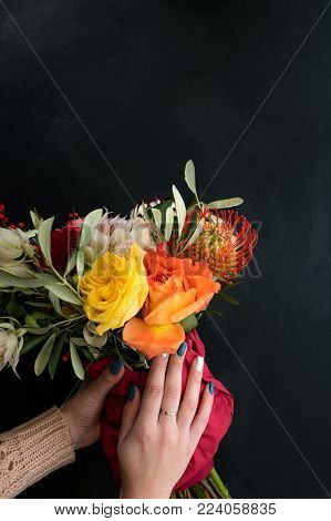 Safe and quick flower bouquet delivery for someone you love. Women hands holding a creative composition of roses dahlia and leaves on black background