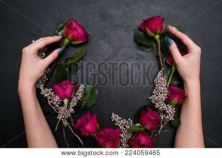 Woman hands composing a wedding wreath from red roses and silver beads on dark background. Stylish and creative adornment for a modern bride