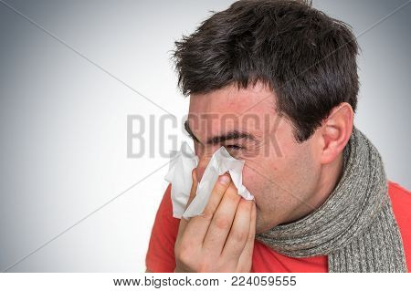 Sick Man With Flu Or Cold Sneezing Into Handkerchief