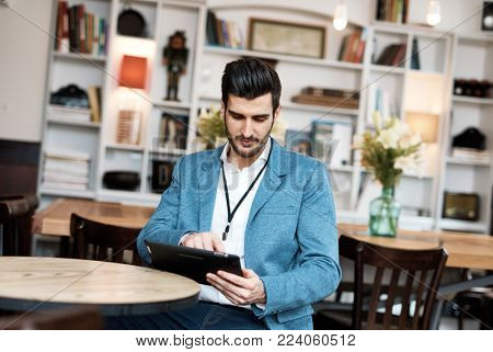 Young businessman sitting at cafeteria, using tablet computer.