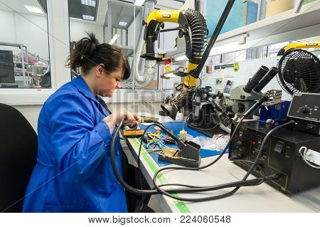 Zelenograd, Russia - October 19, 2017: Women make soldering of radio components to electronic boards. Plant for the production of electronic equipment.