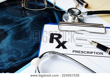 Health care concept. Prescription form and X-ray of the skull on a hospital desk.