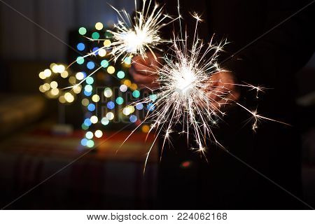 New Year, New Year's Eve. Bengal lights in the hands of a man, colorful bokeh.
