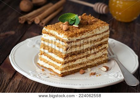 Slice of layered honey cake russian Medovik decorated with mint and almonds on white plate