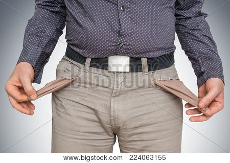 Young man pulling out empty pockets - poor people concept