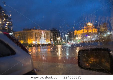 Drops of rain on the window of the car, the lights of the night city in blurring. Rain drops on car glass