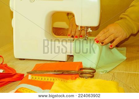 people, needlework, sewing and tailoring concept - tailor woman with thread in needle stitching fabric pieces together. Clothes designer at work in her office. Garment industry, tailoring concept