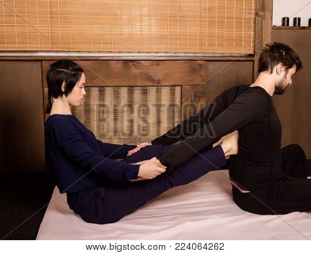 beautiful girl doing thai back massage in spa saloon. Thai massage or Thai yoga massage treatment.