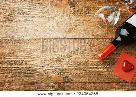 Valentines day background with red wine, wine glass and a card over wooden background, top view