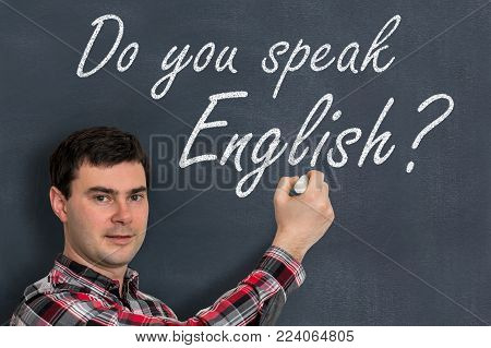 Do you speak English? Man with chalk writing on blackboard - learning language concept