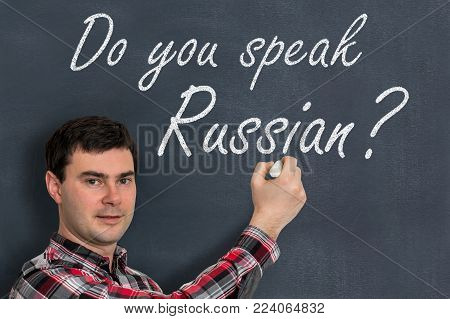 Do you speak Russian? Man with chalk writing on blackboard - learning language concept