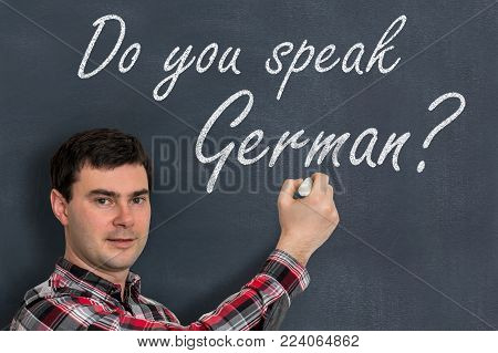 Do you speak German? Man with chalk writing on blackboard - learning language concept