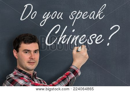 Do you speak Chinese? Man with chalk writing on blackboard - learning language concept