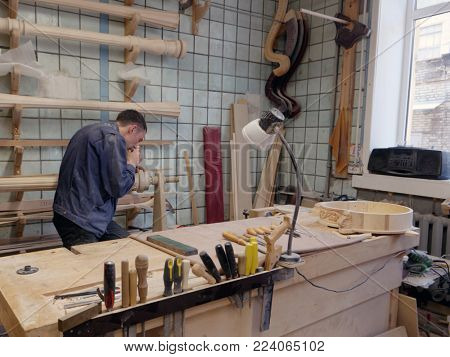 ST. PETERSBURG, RUSSIA - AUGUST 8, 2017: Worker making harp in Resonance Harps enterprise. The company revives the production of harps of the Lunacharsky factory founded in 1947