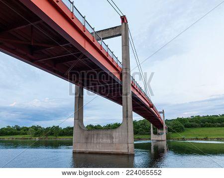 Orange bridge (Jedleseer Steg) across the Neue Donau in Vienna Austria on a cloudy day in summer