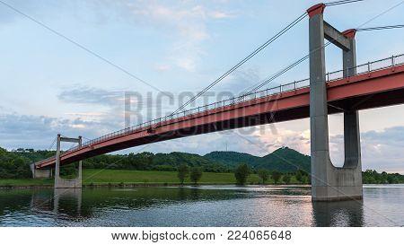 Orange bridge (Jedleseer Steg) across the Neue Donau in Vienna Austria on a cloudy day in summer, Leopoldsberg in the background