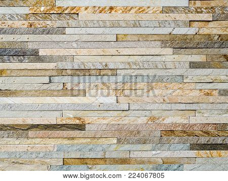 Stacked thin slate brick design background photograph,  multicolor. Thin slate bricks, authentic photograph shot outdoors with natural light. Shades of brown, grey, black and white. Modern, natural luxury style.