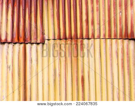 Old patched rusty corrugated tin background photograph. Rustic, country farm style rusted corrugated tin wall with worn white paint. Roughly patched on the side of a shack with great natural patina.