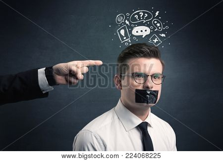 Caucasian business hand pointing at stressed male employee with drawn question, explamation marks, talk bubble above his head