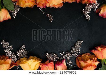 Autumn wedding flowers decor. Orange roses with silver adornment on black background. Elegant and seasonal reception party flower arrangement