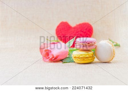 Sweet macaron in cream,yellow and pink violet put overlap with background blurry branch of sweet pink rose and red heart and background clear brown, delicious french's biscuite, sweet scene for valentine's day