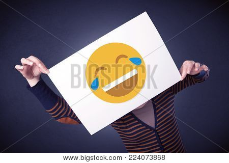 Young casual woman hiding behind a laughing emoticon on cardboard