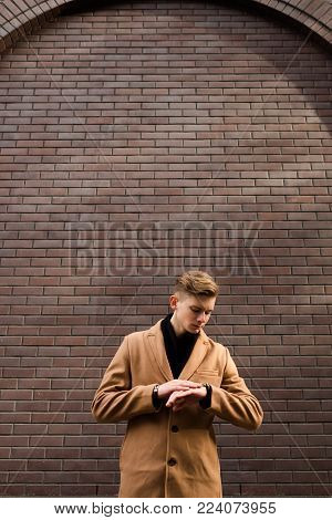 Young casual man looking at watch. Time flies. Girlfriend is late for the date. Waiting for a woman. Anxious and worried expression. Free space concept