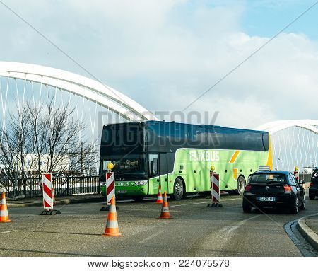KEHL, GERMANY - JAN 16, 2017: VANHOLL Flixbus green bus on the border bridge between Germany and France transporting tourists to France - intercity low-cost, bus service in Europe
