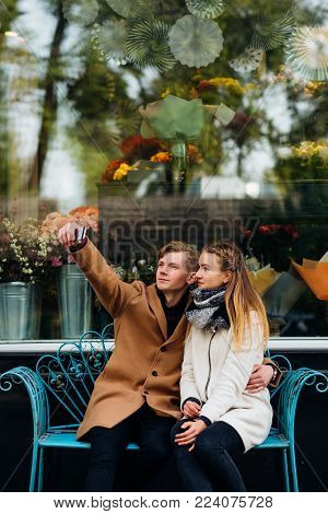 Quick selfie on a romantic date. Modern youth lifestyle. Social network addiction and internet technologies concept