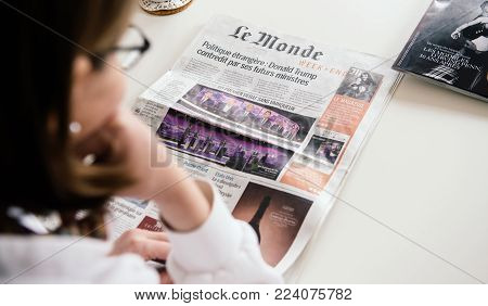 PARIS, FRANCE - JAN 14, 2017: Young French woman reading Le Monde newspaper with cover and article about French presidential debates before Presidential Elections