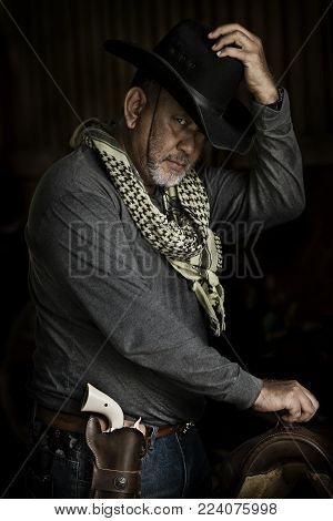 Brave cowboy Handsome old man wearing grey clothes white gun green fabric and catch black hat looking at camera while standing against dark background