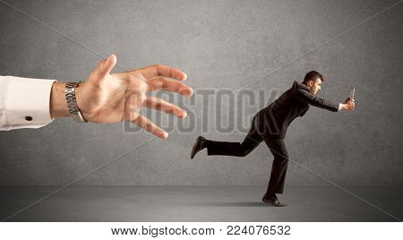 Young miniature businessman running from a big hand with light grey background