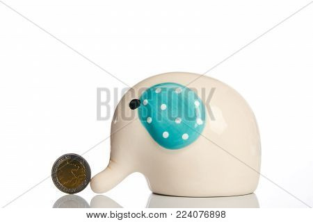 Money box elephant with coin isolated on white background with copy space for text. Saving money concept