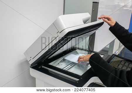 close up businesswoman put documents on printer for scanning and copying in office