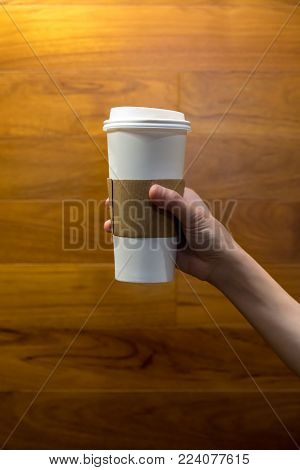 Hands holding single hot latte against wooden background.  Paper coffee cup with plastic lid.