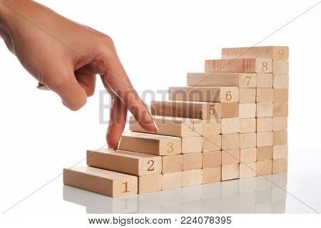 Women hand finger walk on stacked wooden block like stairs isolated on white background, close-up. Business development and growth concept. Take the next steps to your goals
