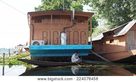 SRINAGAR INDIA - JULY 9 2017 : Lifestyle in Dal lake local people use Shikara a small boat for transportation in Dal lake a famous tourist attraction of Srinagar Jammu and Kashmir state India.