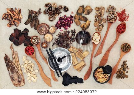 Chinese herbal medicine with traditional herbs, acupuncture needles, moxa sticks used in moxibustion therapy and mortar with pestle on hemp paper background. Top view.