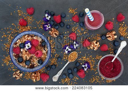 Healthy breakfast super food concept with fruit, nuts, pollen grain, acai berry powder and smoothie,  granola and edible violet flowers with foods high in protein, antioxidants, minerals and vitamins