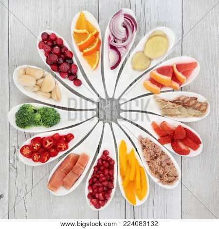 Health food for a healthy heart with fish, vegetables, fruit and herbs on rustic  wood background. Detox superfood concept. High in omega 3 fatty acid, antioxidants, minerals and vitamins.