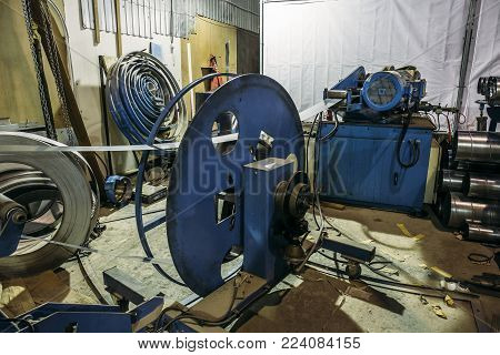 Factory manufacturing of modern metalworking production of industrial steel ventilation air systems, close up of workshop with tools equipment, toned