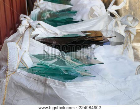 White big bags filled with pieces of sheet  glass for recycle .