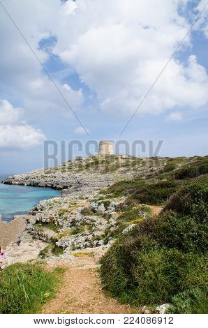 Photograph of a wonderful landscape in Alcaufar, Menorca. A watchtower on the top of the rocks next to the sea with a beach entering.